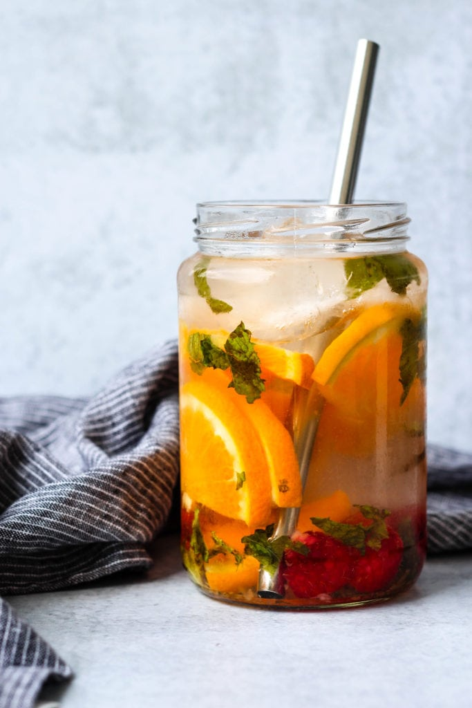 raspberry, orange, and mint infused water in glass jar with metal straw