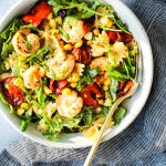 pasta salad with roasted red peppers, cherry tomatoes, corn, shrimp, and arugula in a white bowl, gold fork, and blue dish towel