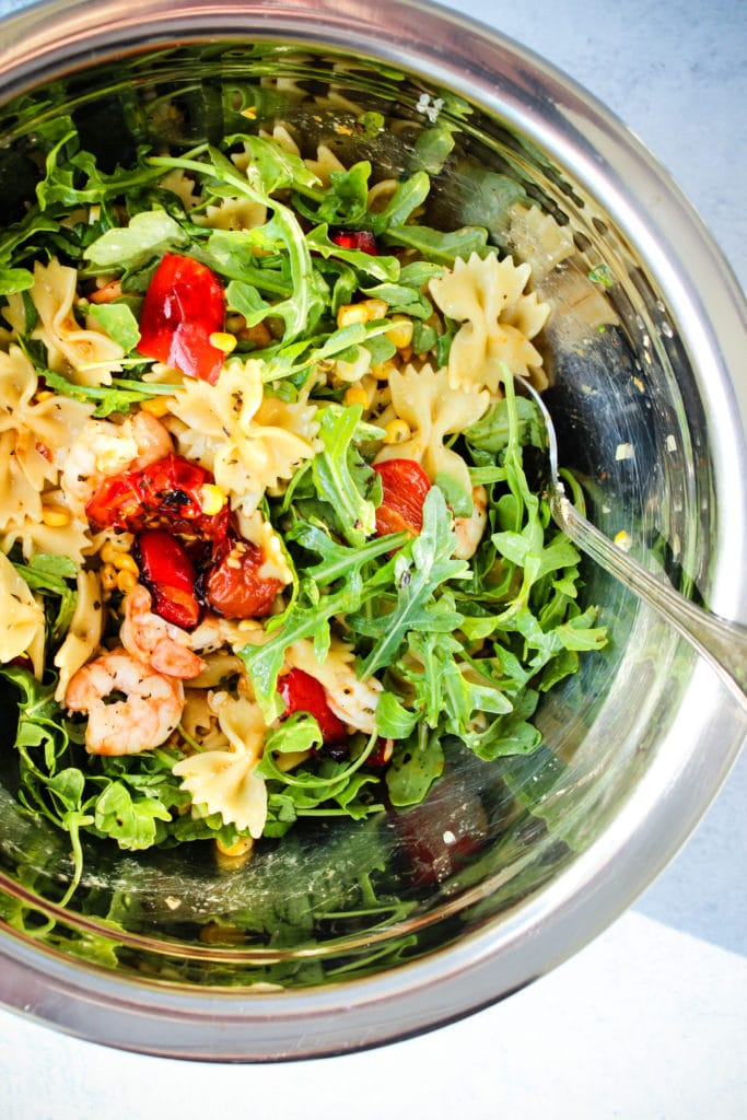 pasta salad with roasted red peppers, cherry tomatoes, corn, shrimp, and arugula in a mixing bowl