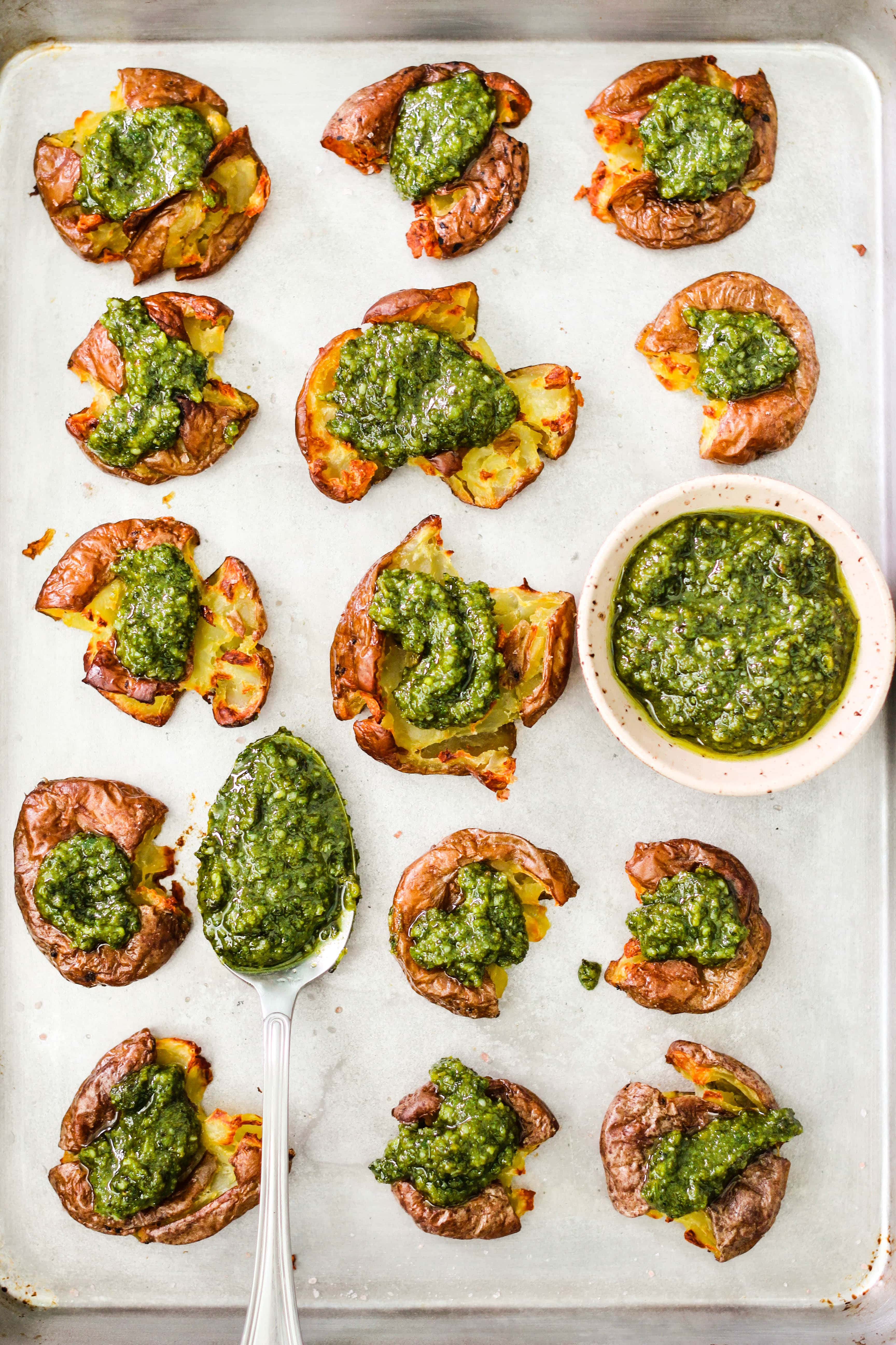 smashed red potatoes topped with pesto on baking sheet with bowl and spoon