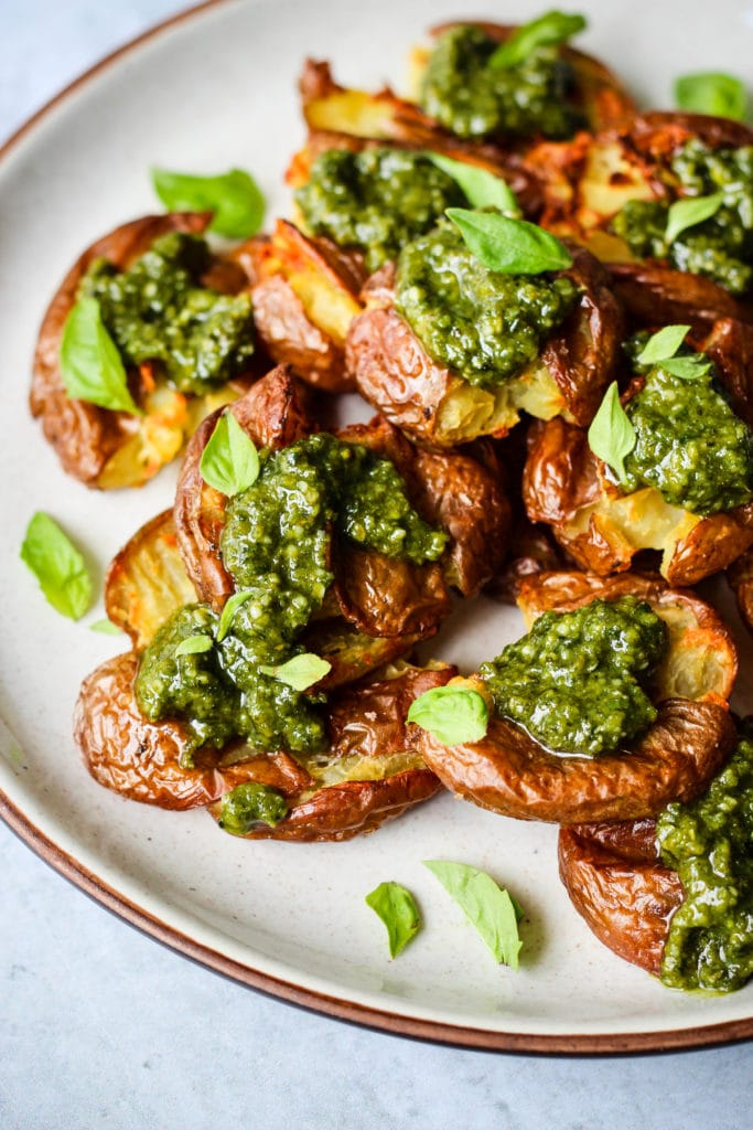 Closeup 45-degree angle photo of smashed red potatoes topped with pesto and basil leaves on white plate.