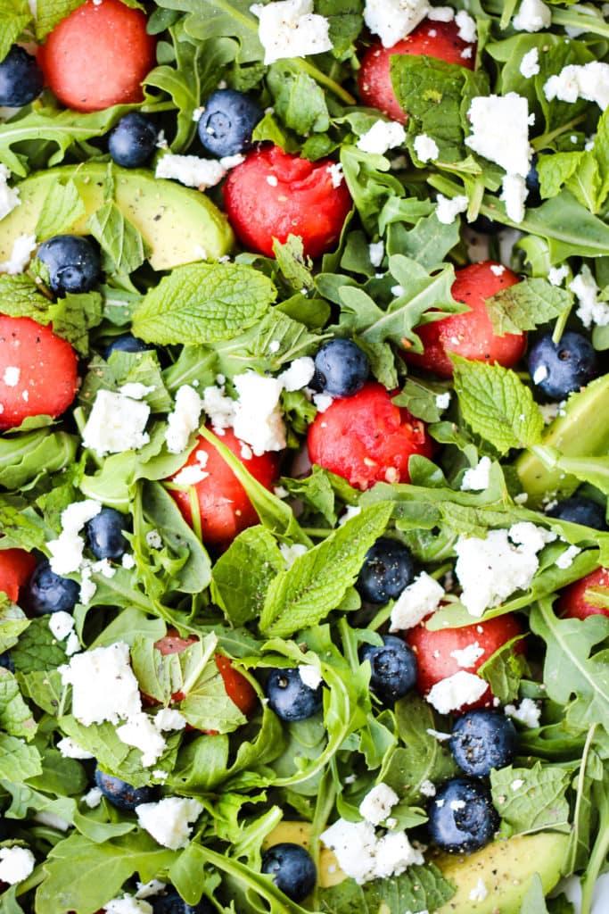 close up of salad with arugula, watermelon, feta, blueberries, avocado