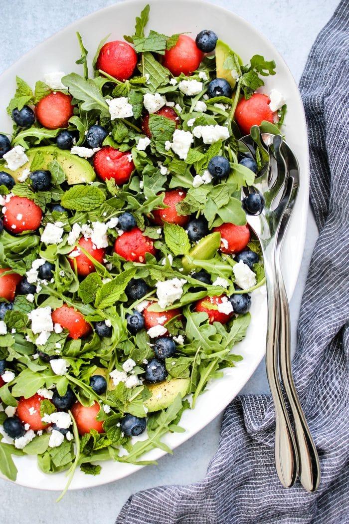 salad with arugula, watermelon, feta, blueberries, avocado on white plate