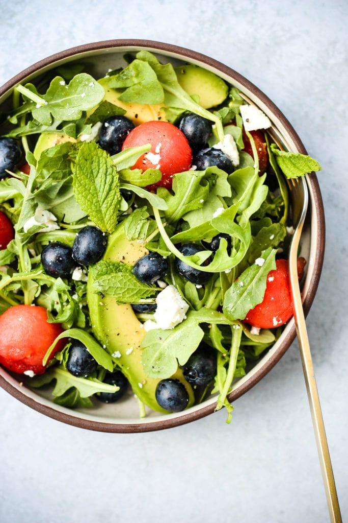 salad with arugula, watermelon, feta, blueberries, avocado in brown bowl