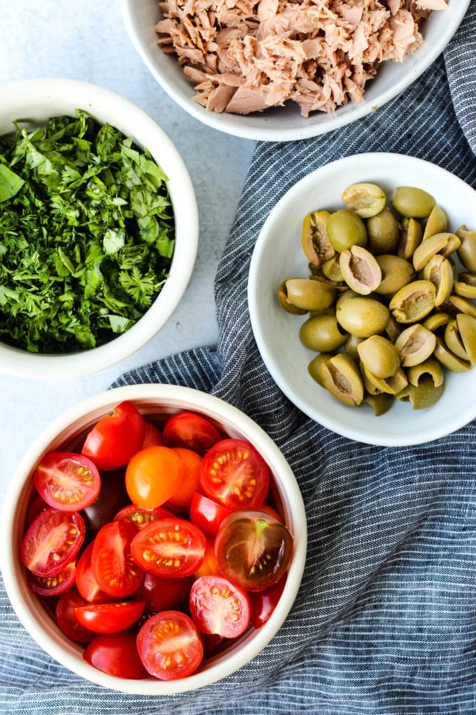 canned tuna, olives, tomatoes, herbs in white bowls