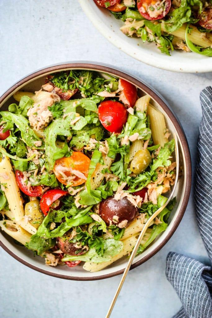 healthy tuna pasta salad with olives, tomatoes, arugula, and herbs