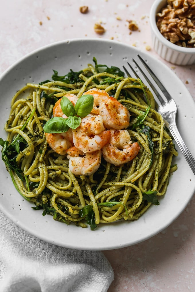 Photo of a white bowl filled with pesto linguine pasta, arugula, and sautéed shrimp.