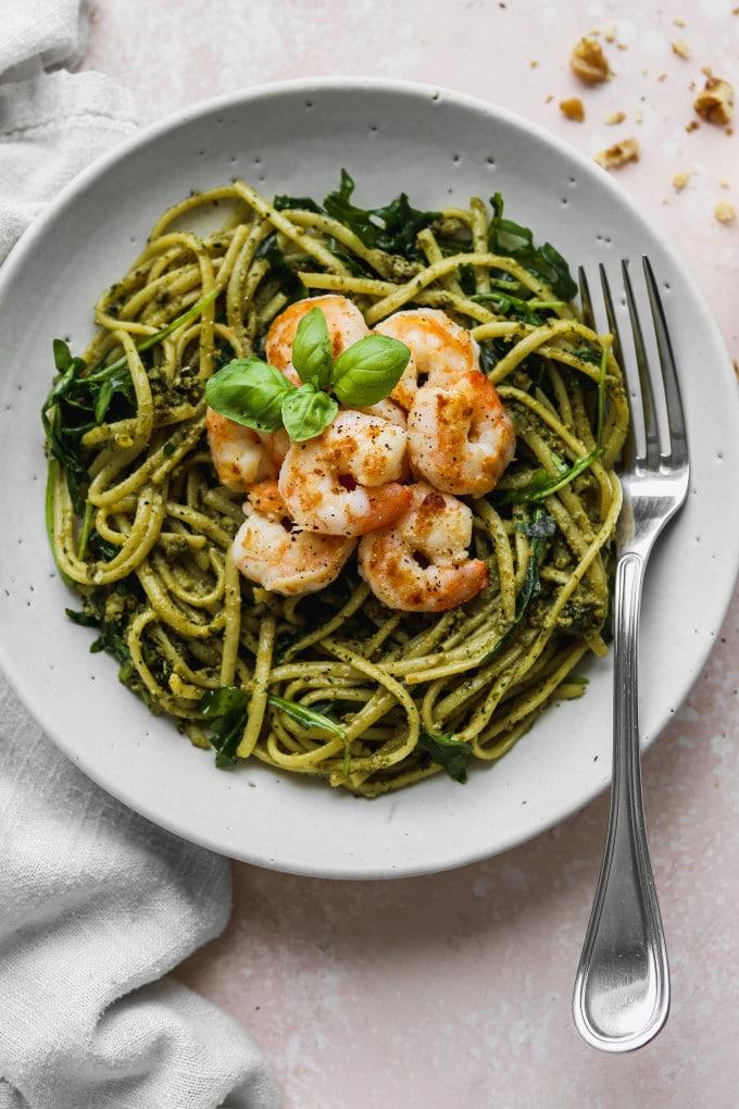 Overhead photo of a white bowl filled with pesto linguine pasta, arugula, and sautéed shrimp.