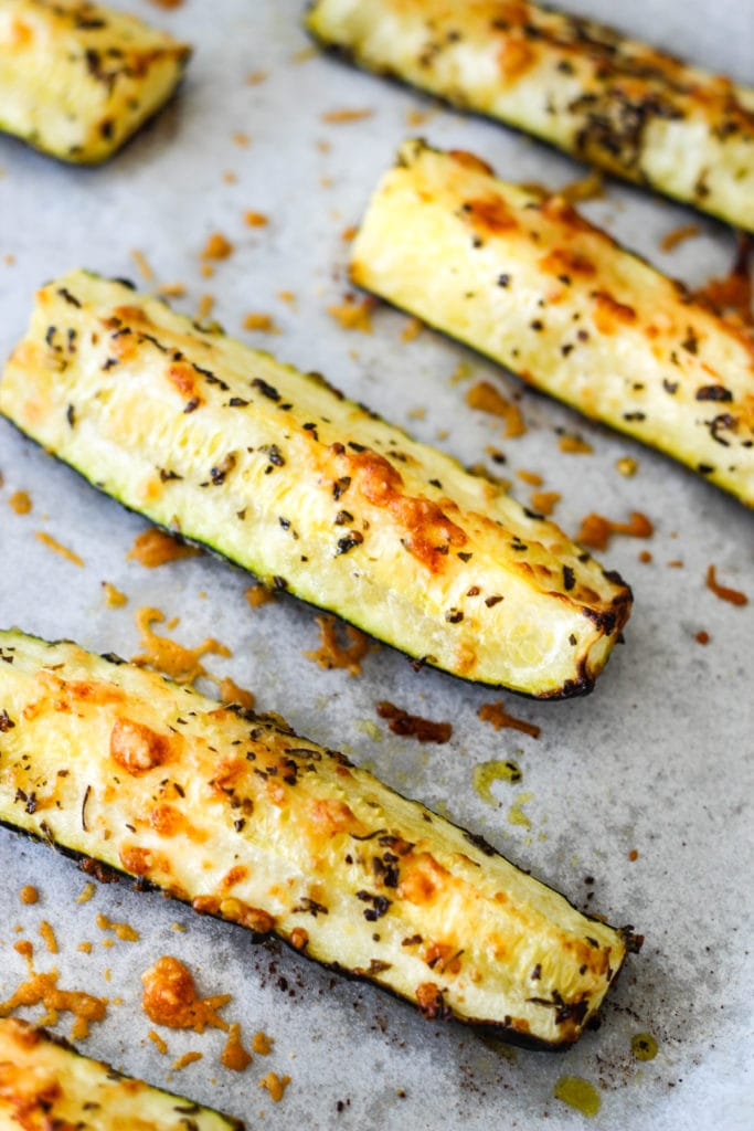 roasted zucchini with parmesan and basil on baking sheet