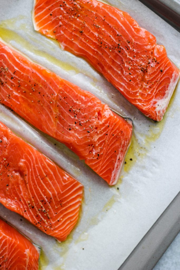 Overhead photo of four un-cooked salmon fillets on a parchment-lined baking sheet.