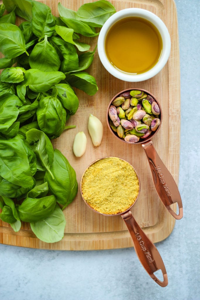 Overhead photo of fresh basil, garlic, olive oil, pistachios, and nutritional yeast on a wooden cutting board.