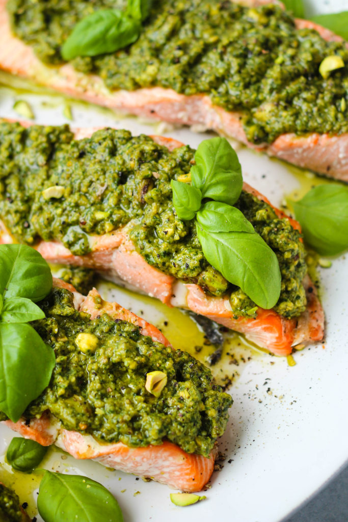Closeup photo of baked salmon topped with pistachio pesto and basil leaves on a large white serving platter.