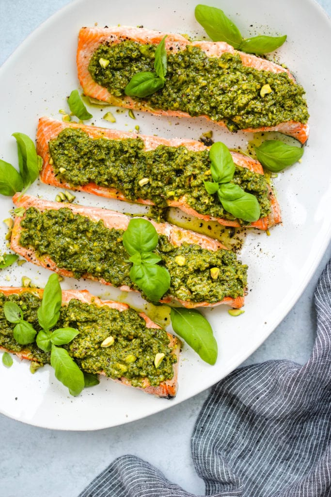 Overhead photo of 4 pieces of baked salmon topped with pistachio pesto and basil leaves on a large white serving platter.