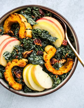 massaged kale salad topped with delicata squash, apples, pecans, and cranberries