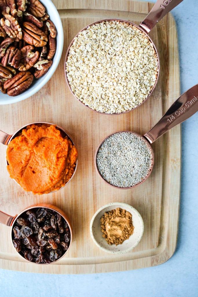 pecans, steel cut oats, pumpkin, chia seeds, raisins, spices on wood cutting board