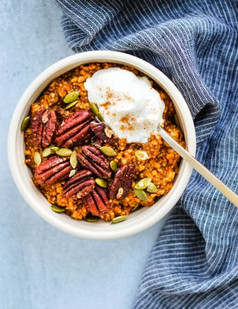 pumpkin pie steel cut oatmeal in small bowl with toasted pecans and yogurt