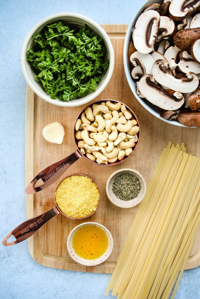 sliced mushrooms, parsley, cashews, garlic, nutritional yeast, thyme, olive oil, and pasta on wood cutting board