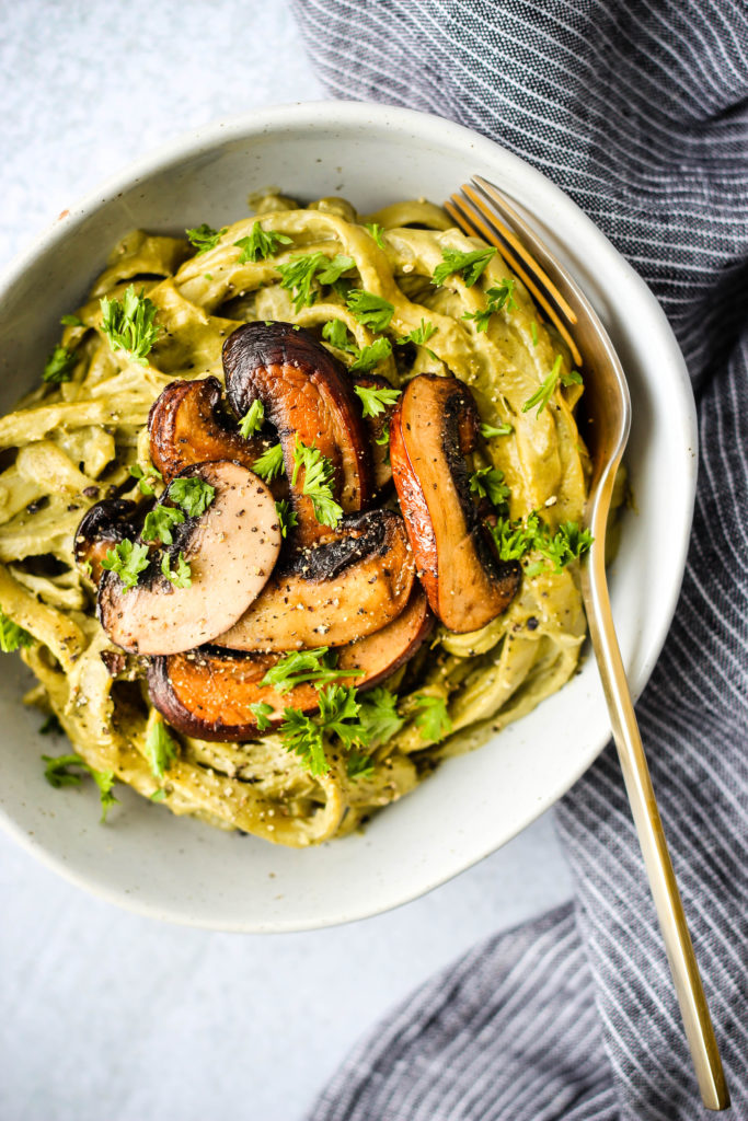mushroom cashew cream pasta topped with mushrooms in a bowl