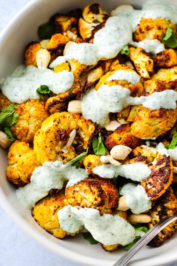 white bowl of curry-roasted cauliflower with mint, cashews, raisins, and yogurt sauce