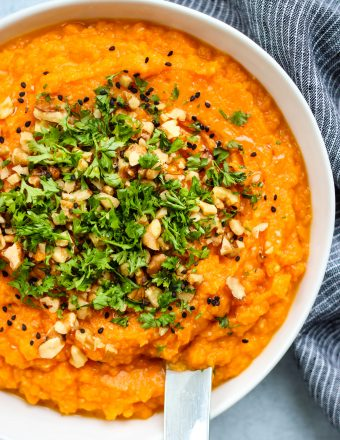 miso mashed sweet potatoes in white bowl topped with walnuts and parsley