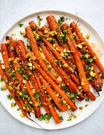 maple-roasted carrots over harissa yogurt sauce with chopped pistachios, parsley, and lemon zest