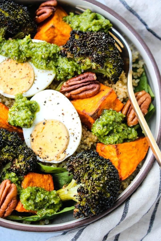 pesto quinoa bowl with sweet potatoes, broccoli, hard boiled egg, pecans