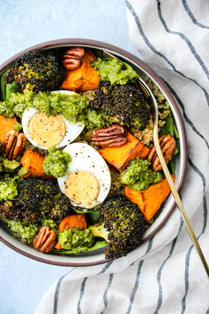 pesto quinoa bowl with sweet potatoes, broccoli, hard boiled egg, pecans