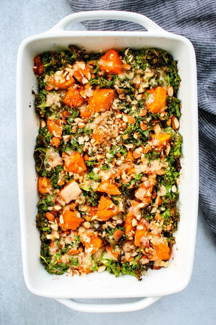 roasted butternut squash with kale, almonds, spicy coconut cream sauce in white casserole dish
