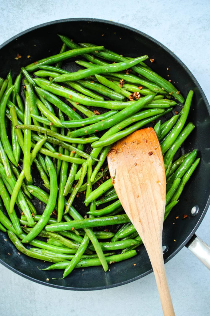 Green beans sautéed in garlic on a frying pan.