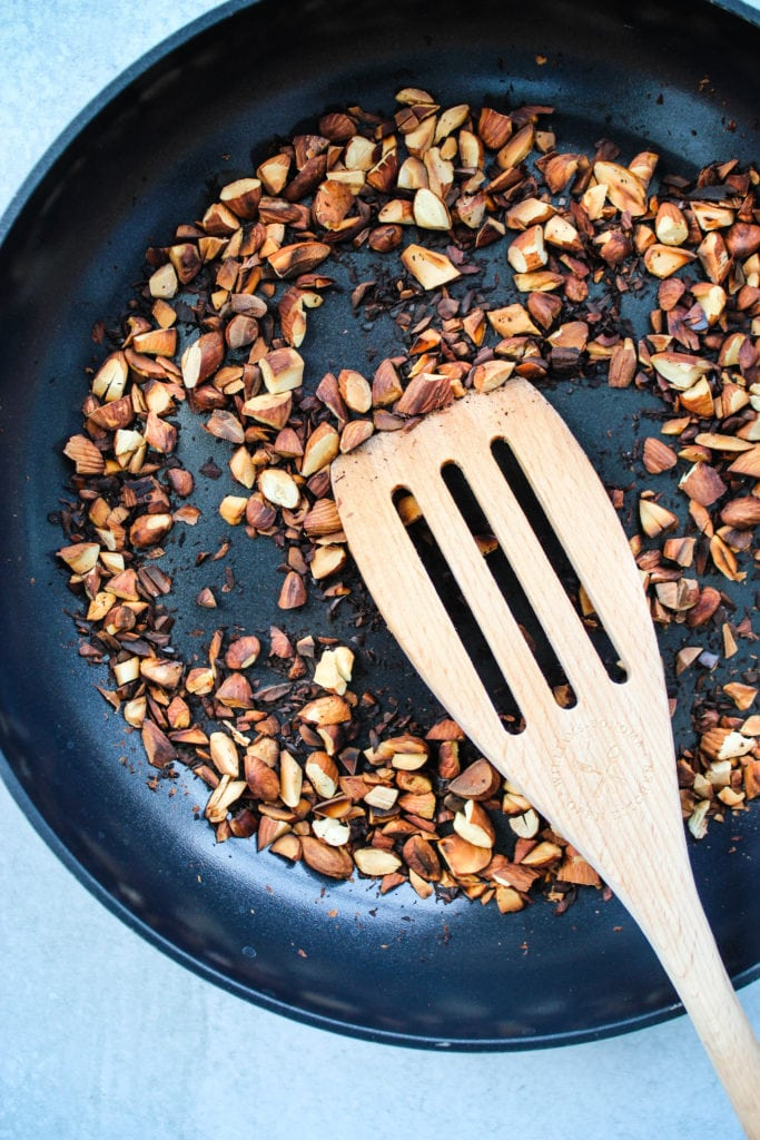 Chopped almonds toasting on a frying pan.