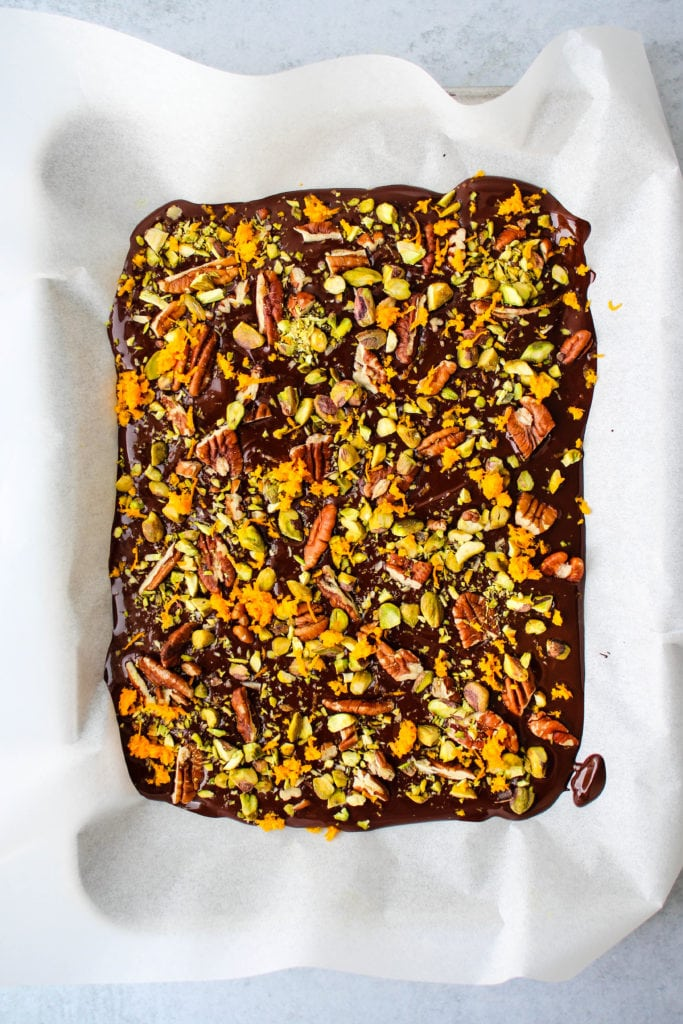 overhead shot of melted dark chocolate topped with orange zest, pecans, and pistachios on parchment paper