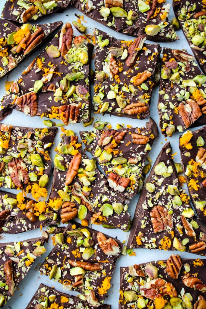 overhead shot of pieces of dark chocolate bark with orange zest, pistachios, and pecans on parchment paper