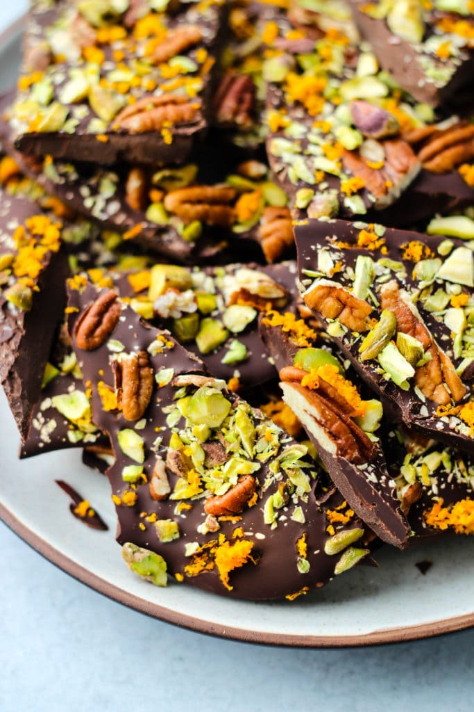 closeup shot of pieces of dark chocolate bark with orange zest, pistachios, and pecans on a plate