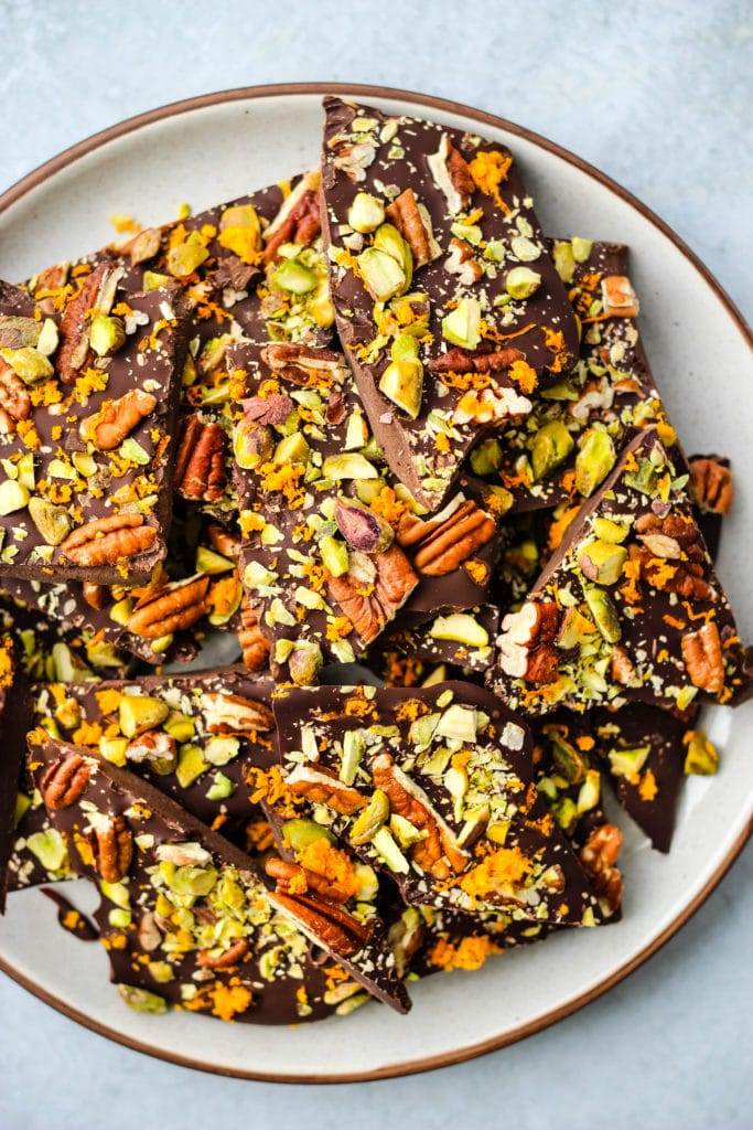 overhead shot of pieces of dark chocolate bark with orange zest, pistachios, pecans on a white plate