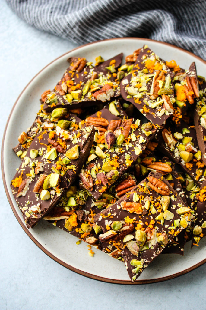 side angle shot of pieces of dark chocolate bark with orange zest, pistachios, and pecans on a white plate
