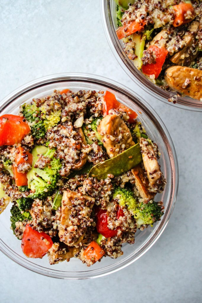 two glass tupperware with tempeh, vegetable, quinoa, and coconut milk stirfry