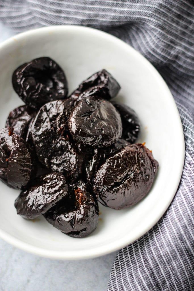 white bowl of prunes