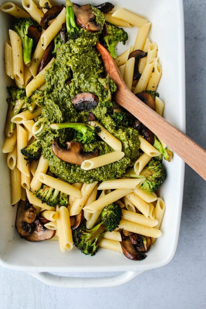 penne pasta in white casserole dish with pesto, mushrooms, broccoli