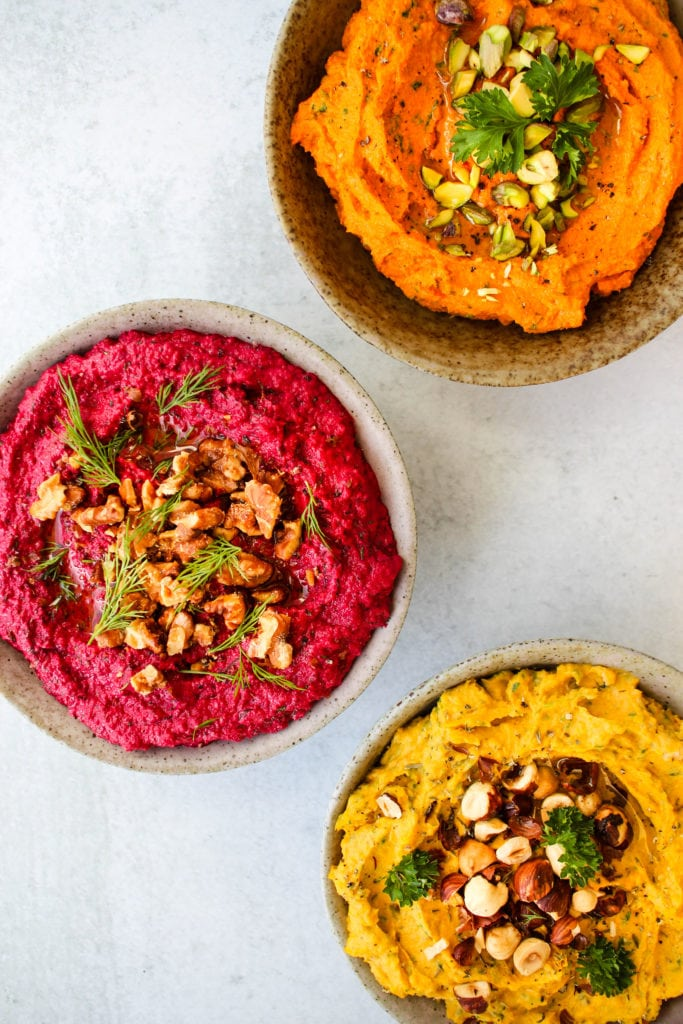 three roasted vegetable dips in small bowls