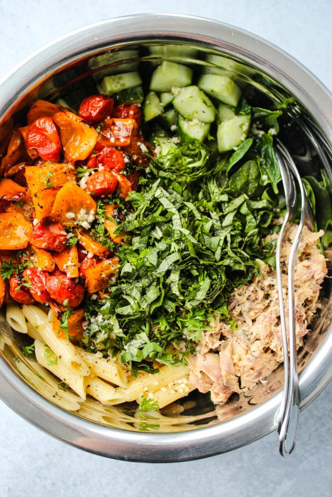 mixing bowl with roasted red peppers, tomatoes, cucumbers, basil, pasta, and canned mackerel