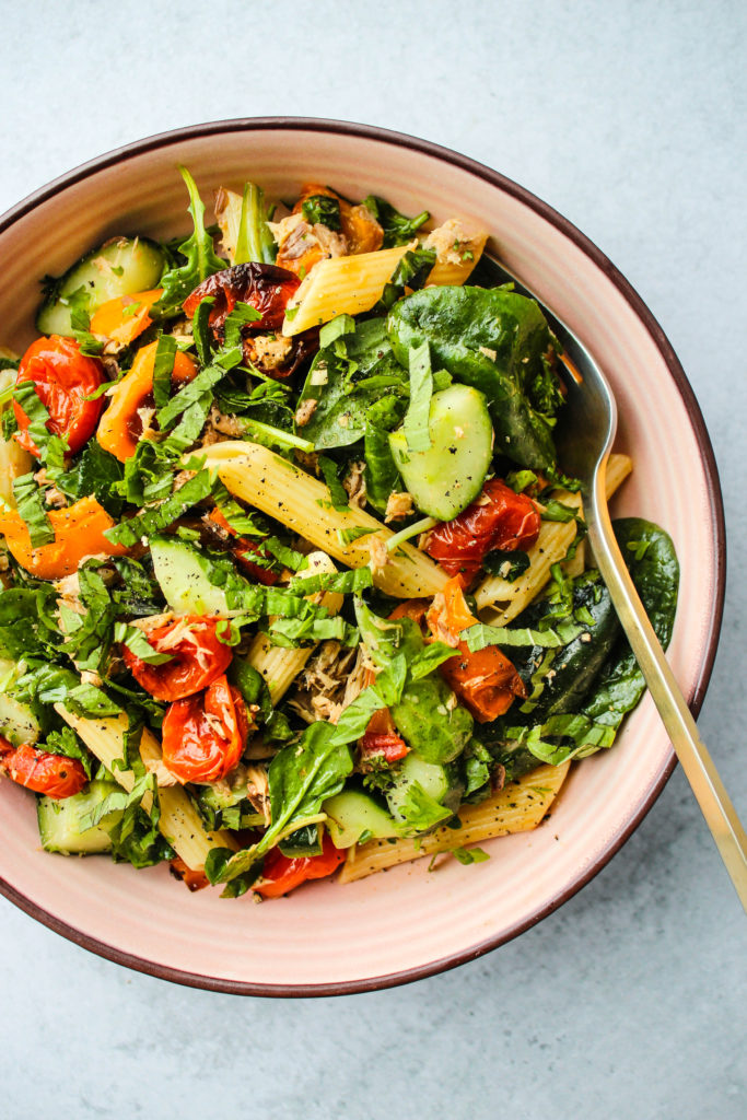 canned mackerel pasta salad with peppers, tomatoes, cucumbers, basil, and arugula in pink bowl