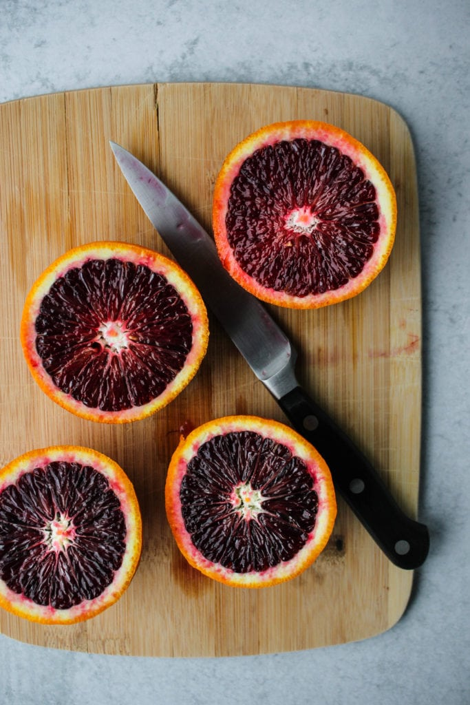 sliced blood oranges on a wooden cutting board