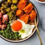grain bowl with roasted sweet potatoes, romanesco, radishes, chimichurri sauce, and a fried egg