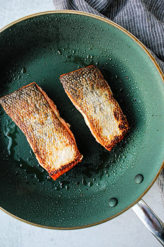 Overhead photo of two crispy salmon fillets with skin-side up on frying pan.