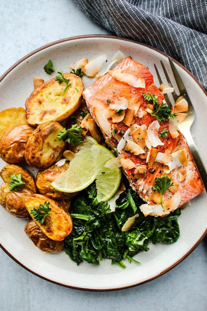 Overhead photo of a white plate with a crispy salmon fillet, potatoes, spinach, coconut, and lime.