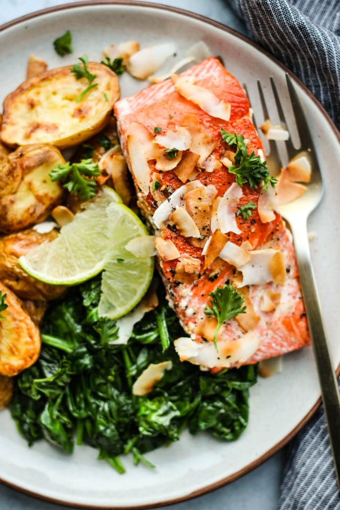 Closeup photo of a white plate topped with a salmon fillet, potatoes, spinach, coconut flakes, and lime.