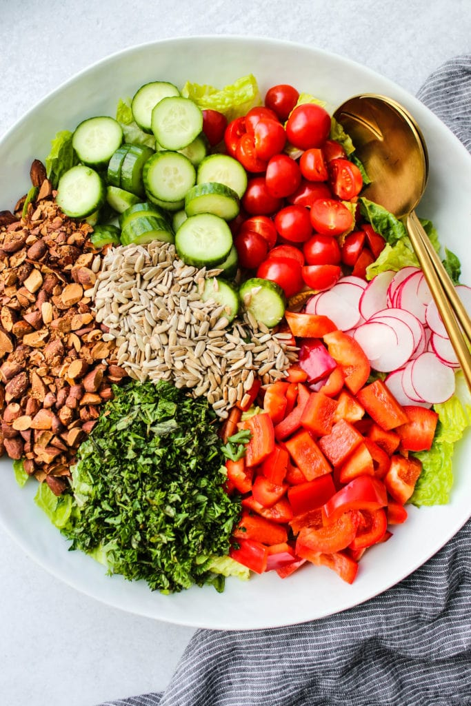 Overhead photo of large white bowl of chopped vegetables, nuts, and seeds.