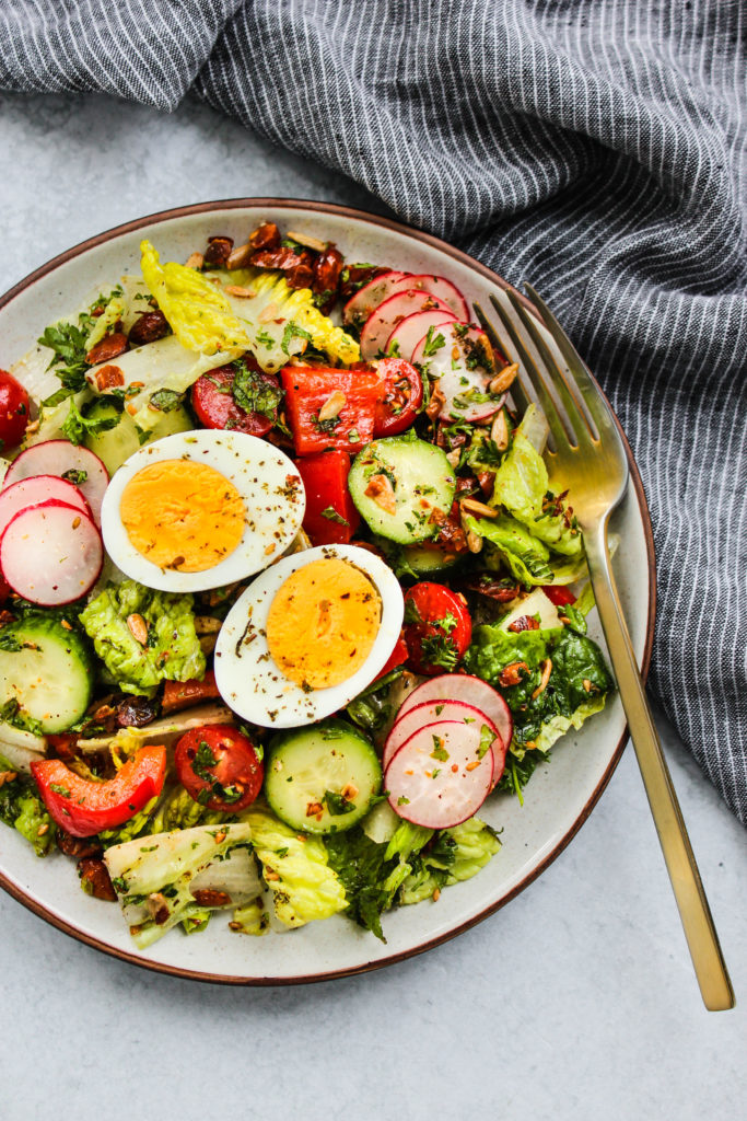 Overhead photo of a plate with chopped romaine and vegetable salad topped with a sliced hard boiled egg.