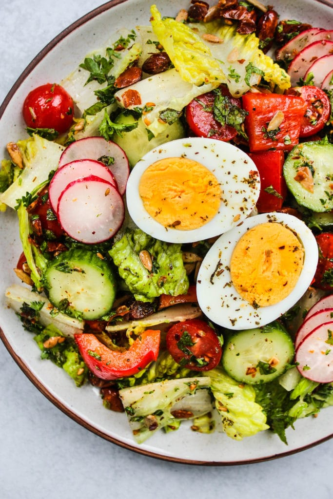 Closeup photo of a plate with chopped romaine salad and a hard boiled egg on top.