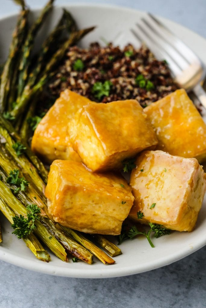 close up of crispy baked tofu topped in maple miso sauce, asparagus, and quinoa on white plate